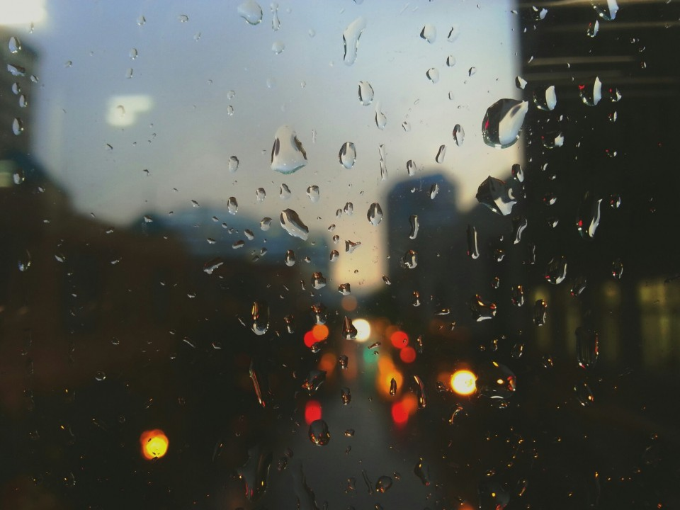 Rain drops on a window with a blurred city view